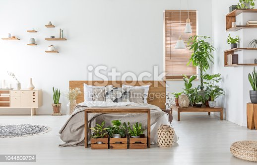 istock Bed with wooden headboard in white spacious bedroom interior with cupboard and plants. Real photo 1044809724