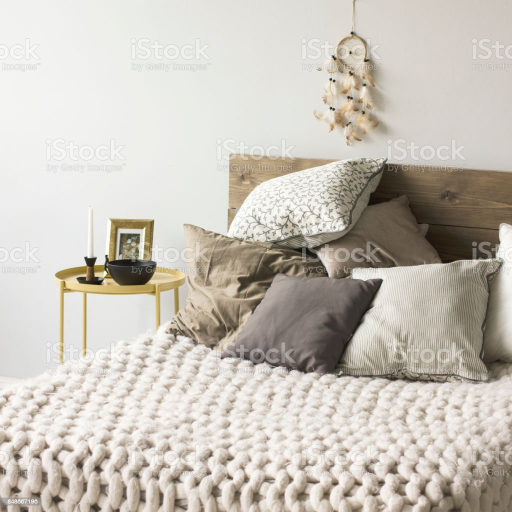 Bed with wooden headboard, pillows, knitted blanket. Scandinavian interior stock photo