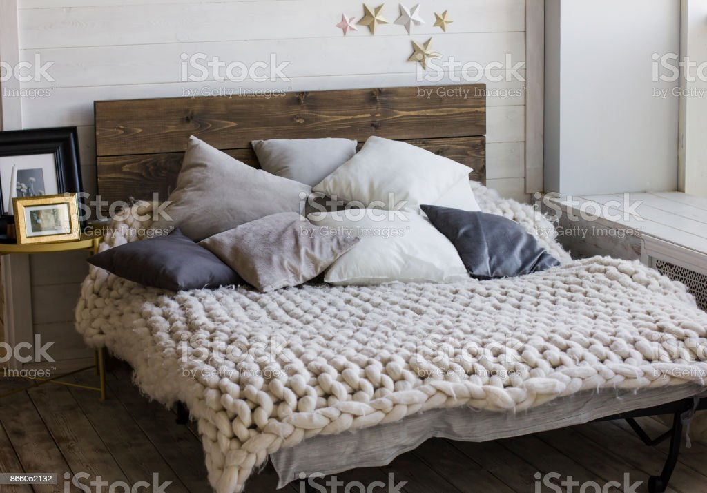 Bed with wooden headboard, pillows, knitted blanket. Scandinavian...