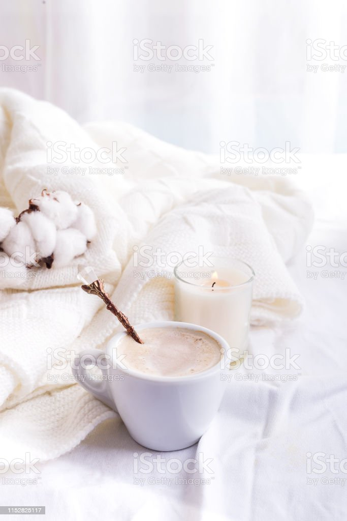 Bedding with a pink fluffy fur plaid and cup of coffee. Copy space....