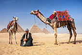 Bedouin with two camels, pyramids on the background, Giza, Egypt.