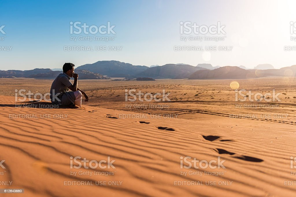 Bedouin looking at sunset in Wadi Rum - foto stock