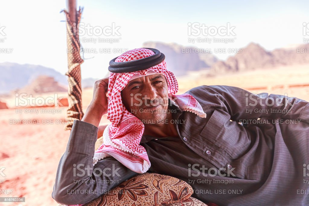 Bedouin man or Arab man in traditional outfit, lying down on the couch, desert background. stock photo