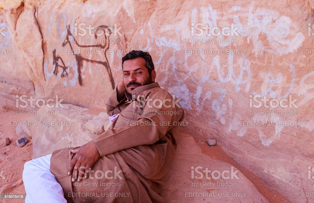 Bedouin man or Arab man in traditional outfit, lying down on the rock. stock photo