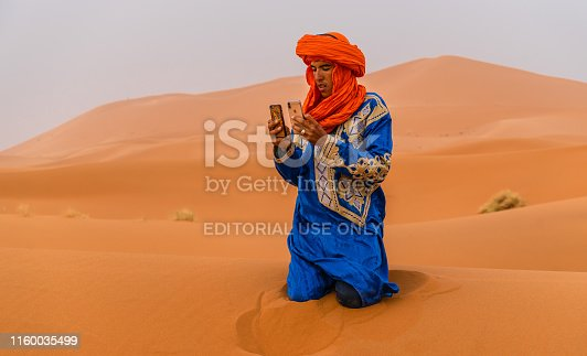 Merzouga, Morocco - May 01, 2019: Bedouin man take a picture with phone in Sahara desert