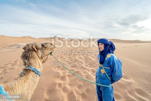Sahara Desert, Morocco - March 16, 2020: A Bedouin man wearing blue and camel on sand dunes of Sahra Dessert
