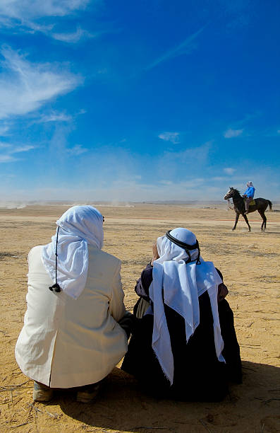 Bedouin Men and Horse Men sitting in the desert with horse in the distance. negev stock pictures, royalty-free photos & images