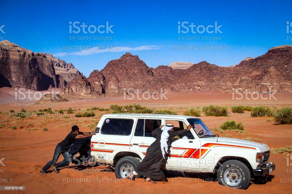Bedouin men push a 4WD Landcruiser in Wadi Rum, Jordan stock photo