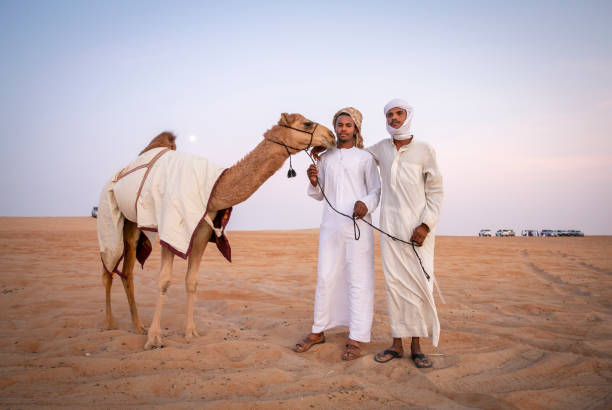 Bedouin men with their camel in a desert stock photo
