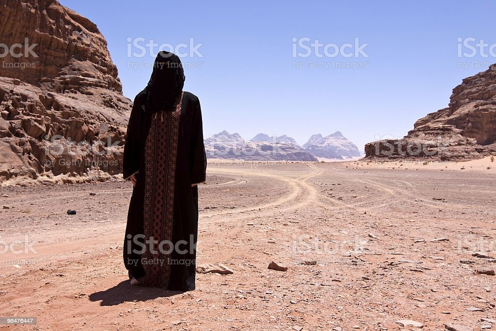 Bedouin woman with burka in the desert royalty-free stock photo
