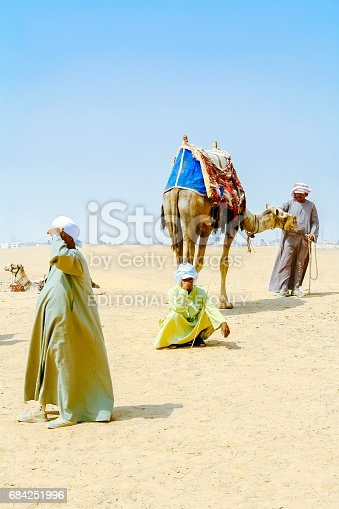 883177796istockphoto Cairo, Egypt - August 13, 2006: Bedouins with camels in desert Sahara. Giza. Egypt. UNESCO World Heritage 684251996