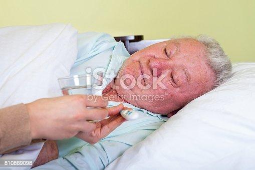 istock Bedridden elderly man having high temperature 810869098