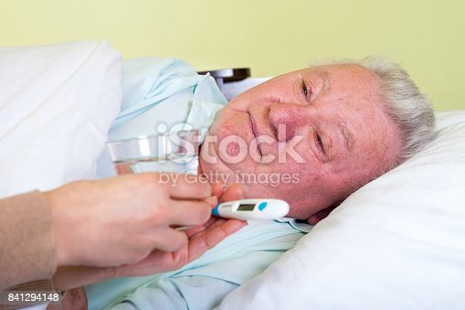 istock Bedridden elderly man having high temperature 841294148