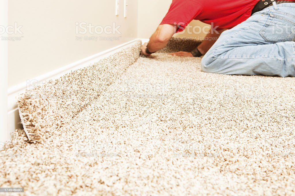 Bedroom Carpet Installation with Worker Cutting stock photo