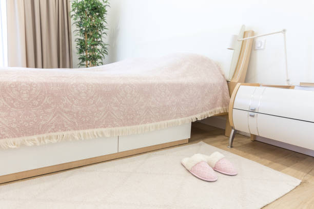 Bedroom in modern style with pink cozy soft slippers on floor stock photo