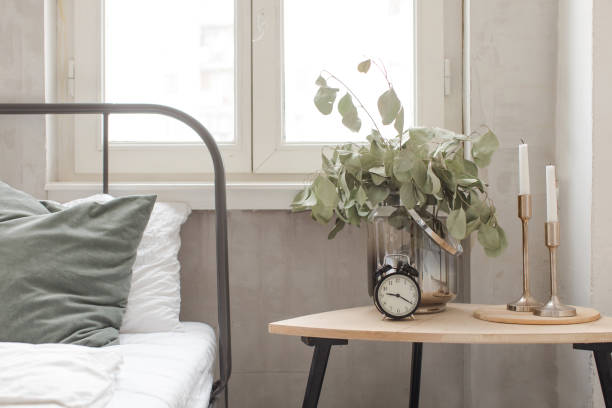 Bedroom interior clock plant pot on wooden table stock photo