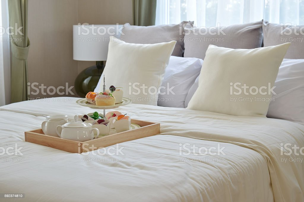 bedroom interior with decorative tea set and dessert on bed stock photo