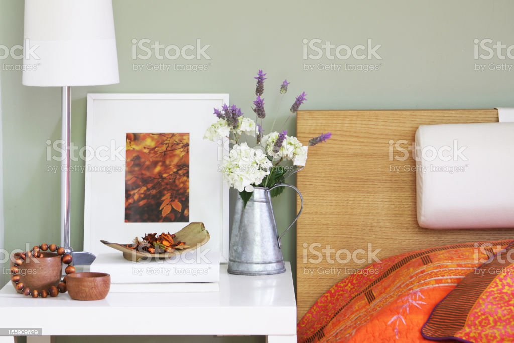 Bedroom night table with lamp, decor and flowers stock photo