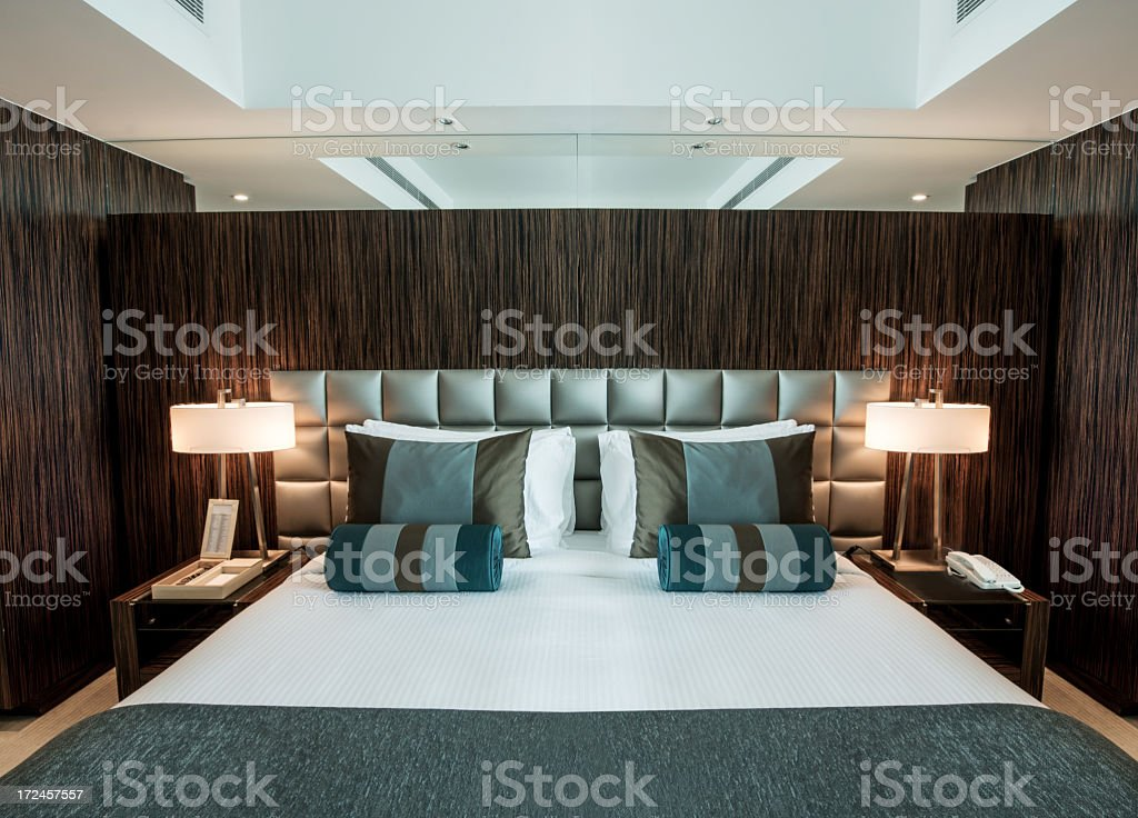 Bedroom with black walls and blue sheets royalty-free stock photo