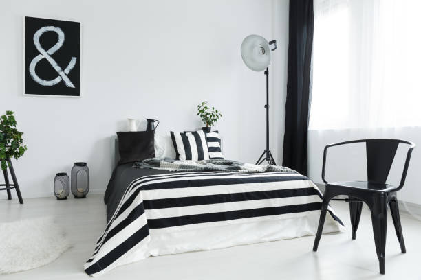 Bedroom with chair Stylish, black and white bedroom with black, designer chair designer baby stock pictures, royalty-free photos & images
