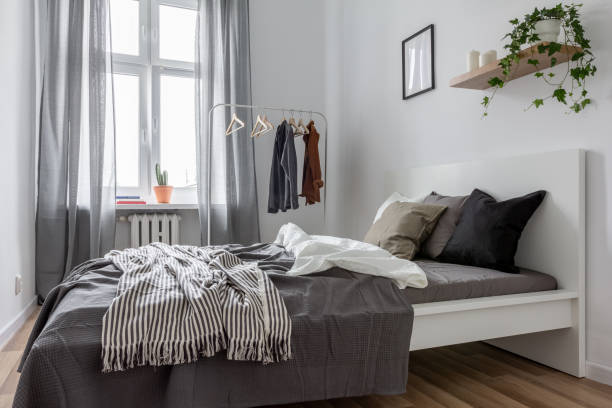 Bedroom with clothes rack Contemporary bedroom with gray window curtains and clothes rack bachelor stock pictures, royalty-free photos & images