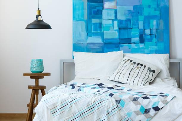 schlafzimmer mit modernen blauen kunstwerk - paletten kopfbrett stock-fotos und bilder