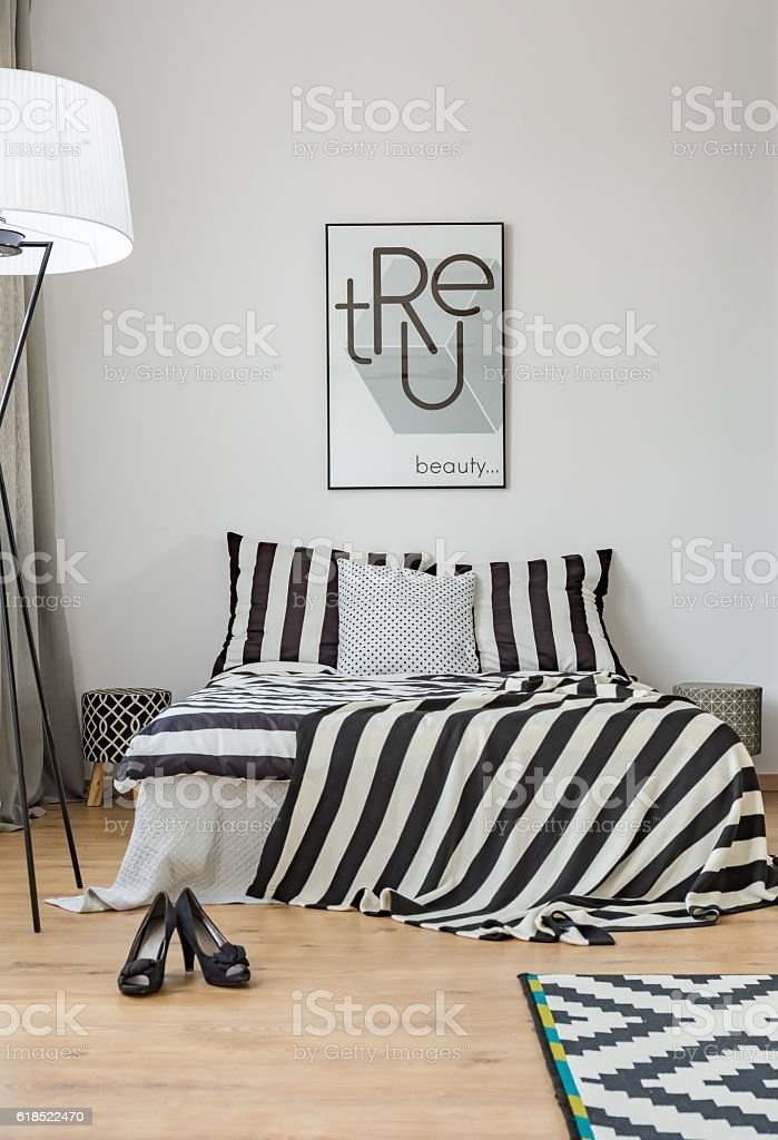 Light bedroom with pattern bedding and picture on the wall