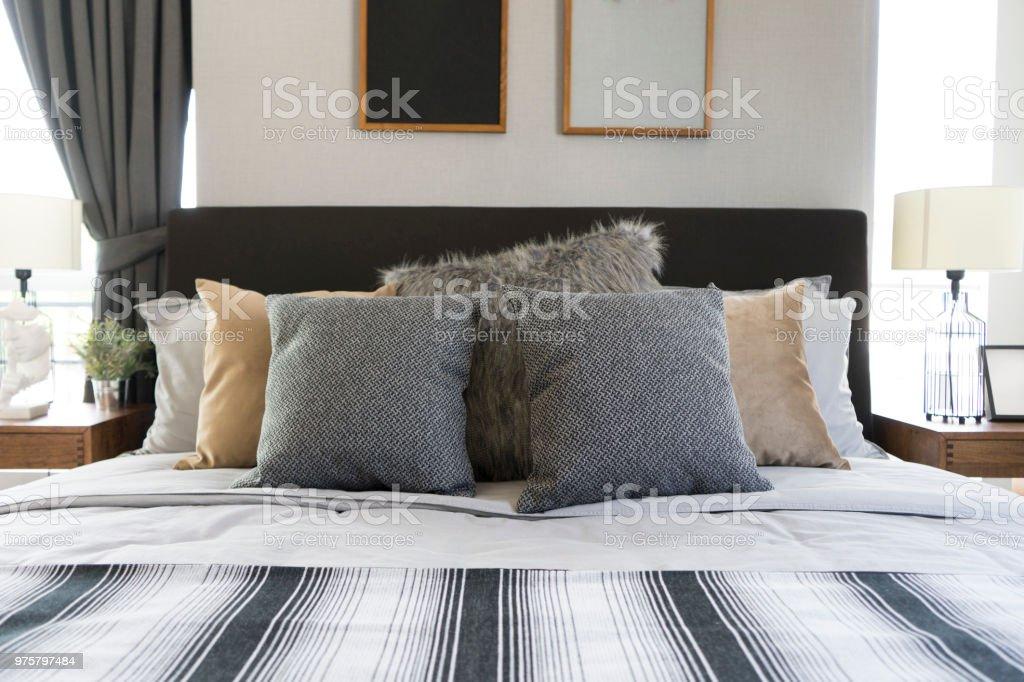Schlafzimmer mit Bilderrahmen an Wänden mit zwei grauen Kissen - Lizenzfrei Architektur Stock-Foto