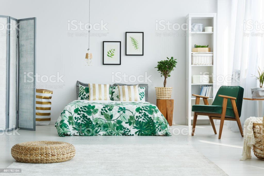 Bedroom with screen, bed, armchair stock photo