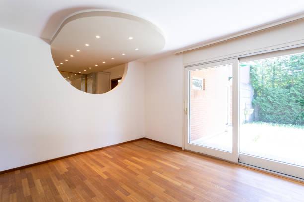 Schlafzimmer mit weißen Wänden und Parkett. Bogen mit Scheinwerfern – Foto
