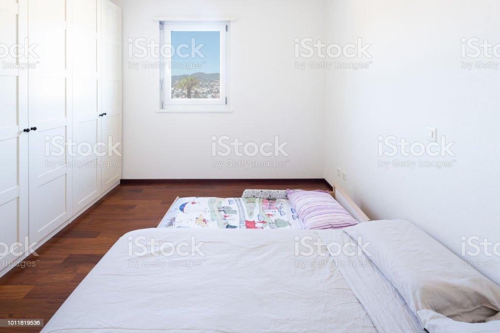 Dormitorio Con Ventana Y Cama En El Suelo Foto De Stock Y