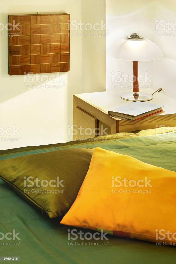 Bed-room's details: pillows, lamp, bedside table, book, wood wall art royalty-free stock photo
