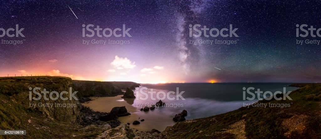 Bedruthan Steps at Night A night time scape looking south across Bedruthan Steps in Cornwall. This is a well known beach close to Newquay and a popular areas for tourist and beach goers. The photograph shows the rocky bay with waves crashing on the beach and the Milky Way in the background. Astronomy Stock Photo