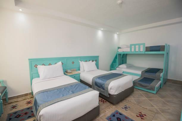 betten in einem luxus-familienzimmer eines hotelzimmers - etagenbett weiss stock-fotos und bilder