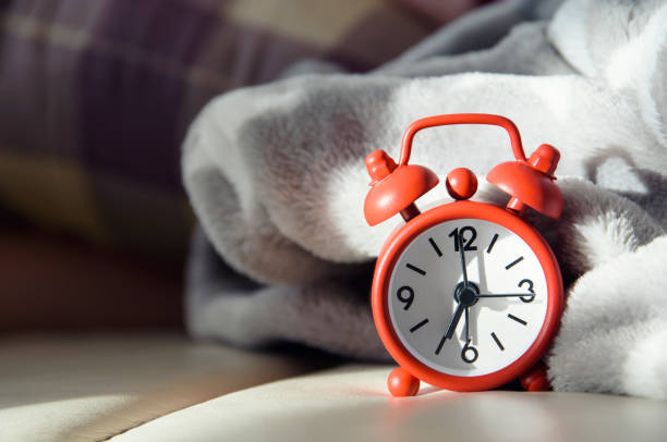 Bedside alarm clock with morning light stock photo