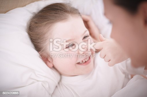 Closeup of a mother putting her smiling young daughter to bed