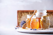 istock Bee pollen granules, honey jar with wooden dropper, honeycomb on grey backdrop. Copy space. Autumn harvest concept 1176629924