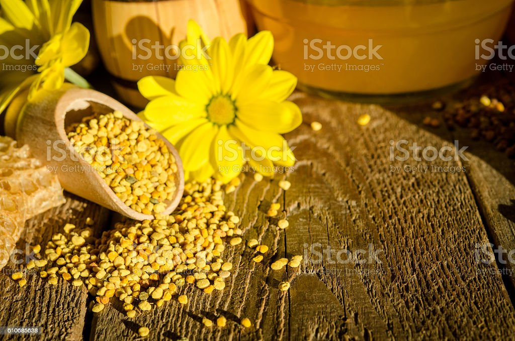 Bee pollen granules  in wooden scoop and flowers on table stock photo