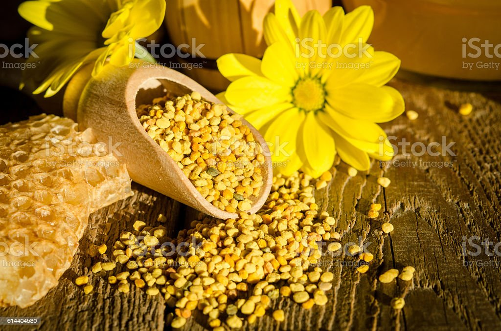 Bee pollen granules  in wooden scoop, honeycombs and flowers stock photo