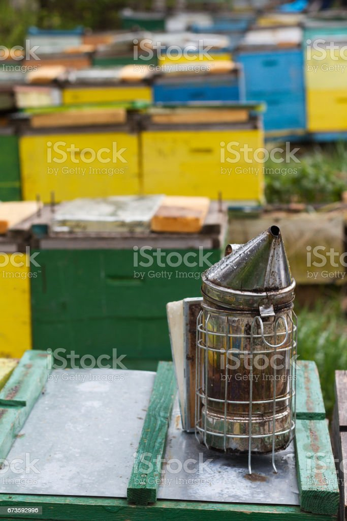 bee smoker on top of beehives boxes stock photo