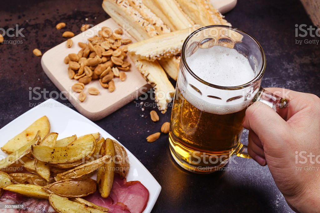 Beear glass in hand Plate with baked potatoes and meat, salted peanuts scattered and cheese sticks to beer. Beer glass with light beer in a man's hand. Adult Stock Photo