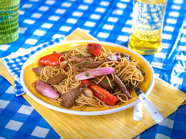 Beef and noodle stir fry, Tallarin Saltado, typical Peruvian dish Beef and noodle stir fry, tallarin saltado, a typical Peruvian dish served on yellow plate in picnic setting with blue and white checked table cloth peruvian culture stock pictures, royalty-free photos & images