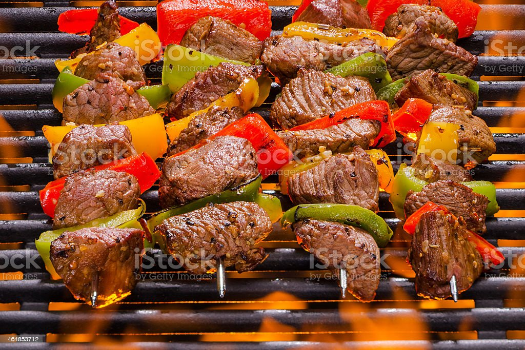 Beef and pepper kebabs roasting on a barbecue grill stock photo