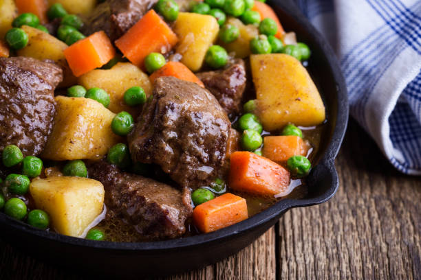 Beef and vegetable stew with potatoes Beef and vegetable stew with potatoes in cast iron skillet on rural table beef stew stock pictures, royalty-free photos & images