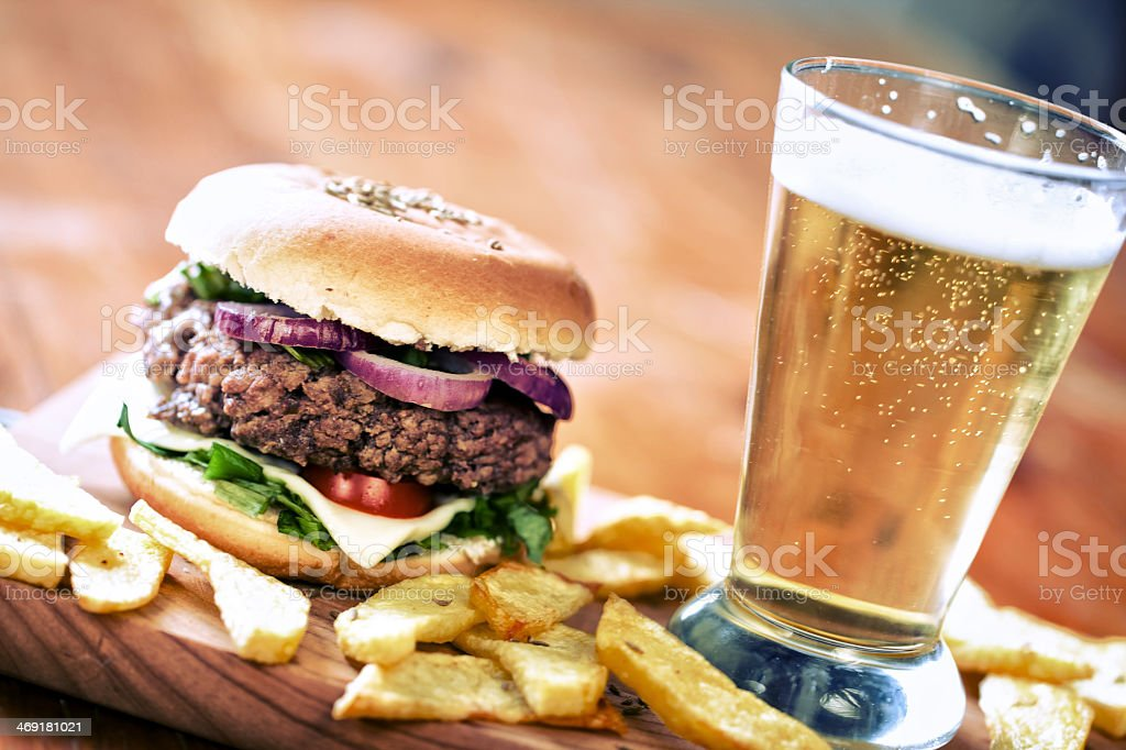 Beef bagel hamburger with potato wedges and fresh beer stock photo