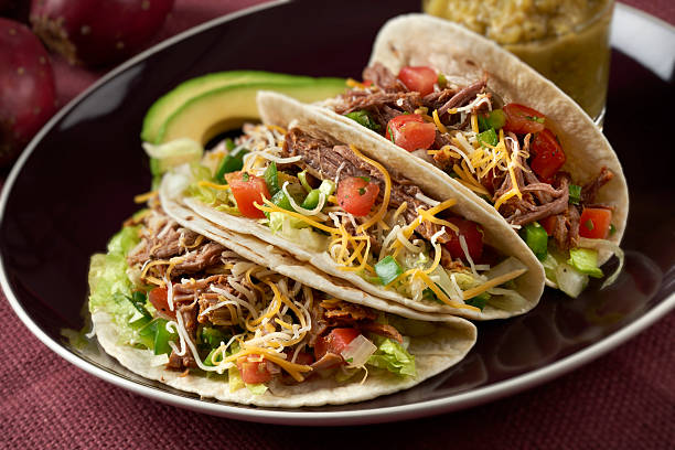 Beef Barbacoa Tacos Three beef barbacoa tacos in soft tortillas.  Made with spicy shedded beef, lettuce, tomatoe, onion and cheddar cheese and served with a green salsa and avocado slices. burwellphotography stock pictures, royalty-free photos & images
