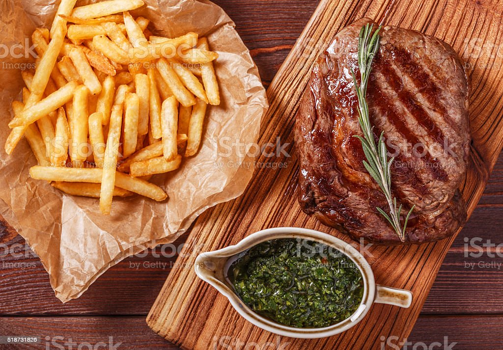 Beef barbecue ribeye steak with chimichurri sauce, french fries. stock photo