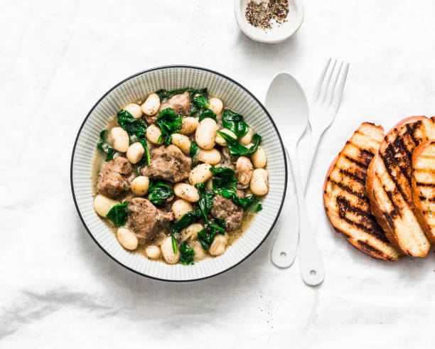 beef, beans, spinach stew on a light background. delicious homemade comfort food - fagioli cannellini foto e immagini stock