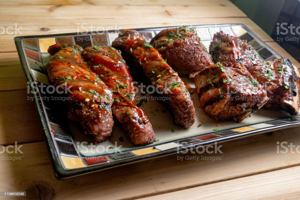 Beef Boneless and Bone-in Ribs in Barbecue Sauce on a Rustic Platter stock photo