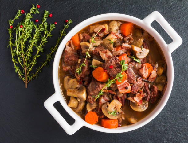 Beef Bourguignon in a casserole on black stone. Beef Bourguignon in a casserole on black stone. Stewed with bacon, garlic, carrots, onions, mushrooms,  red wine, fresh thyme and spices. Top view. stew stock pictures, royalty-free photos & images